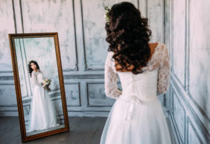 Разглядывать платье в зеркале